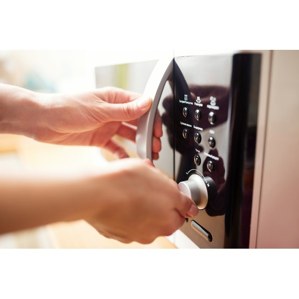 A woman is turning the knob on her microwave oven.