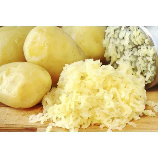 A potato ricer sits next to riced potatoes and some boiled potatoes.