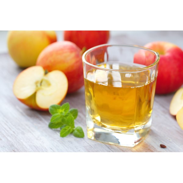 A small cup of apple juice beside a pile of apples.