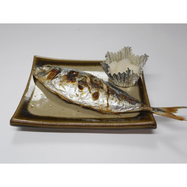 A pan grilled trevally sits on a plate.