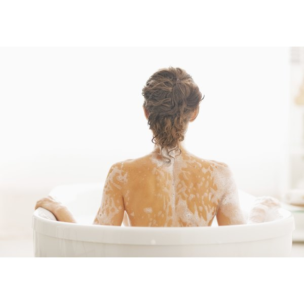 A woman has soap bubbles on her back.