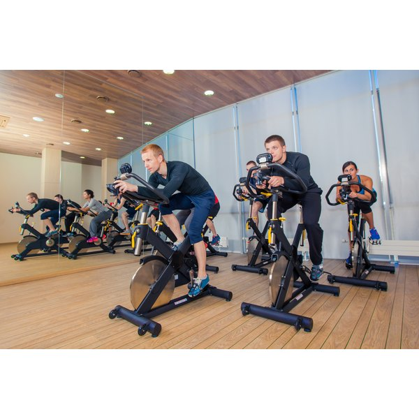 A group of people are in an indoor cycling class.