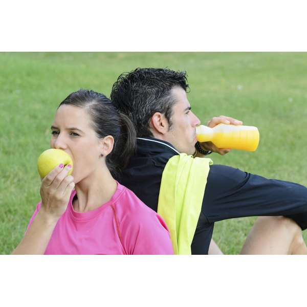 Male and female athletes sitting back to back having a snack.