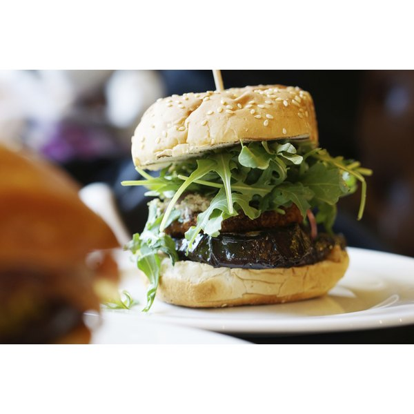 A gourmet-style venison burger sits on a white plate in a restaurant.