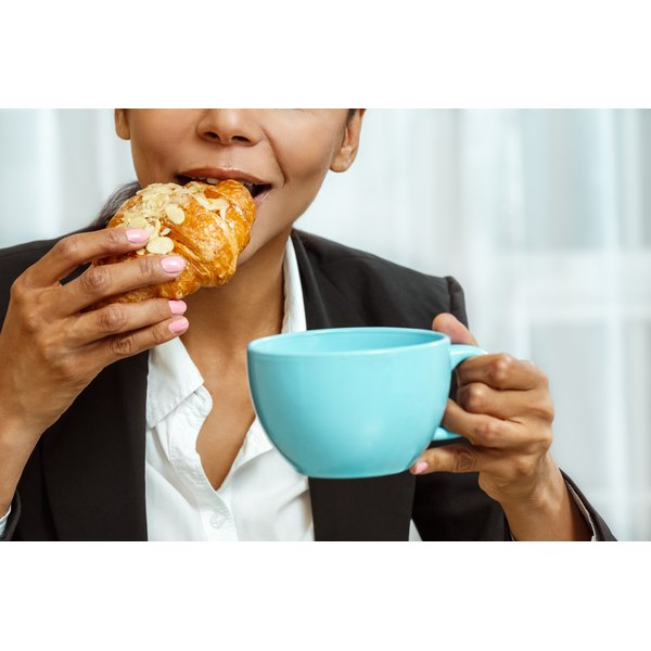 A woman eats a crescent roll before heading out to work.