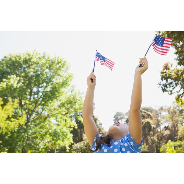 Young girl waving American flags