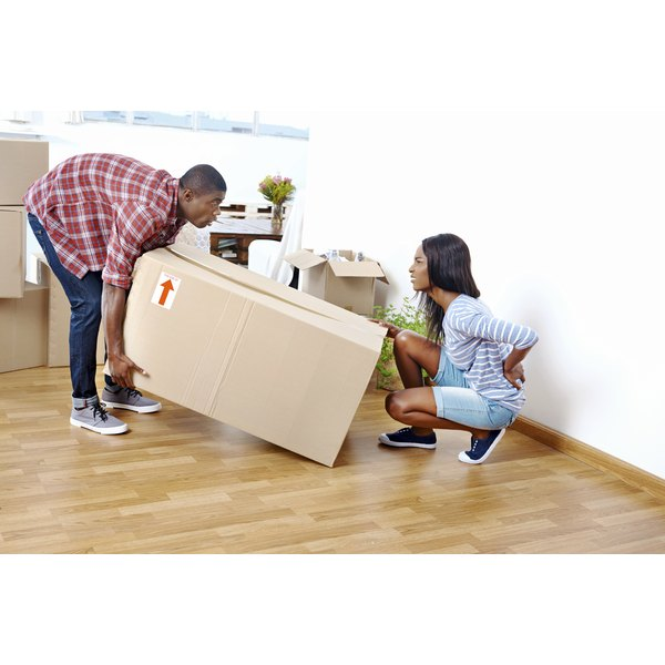 A woman experiences pain as she was lifting a box with her father in their home.