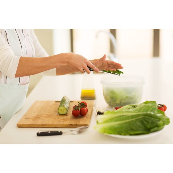 A woman cutting vegetables and placing them in a plastic container.