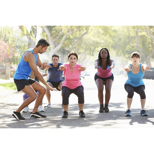 A group of people exercise outside with a trainer.