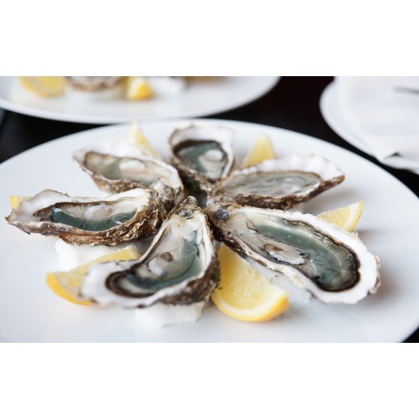 A plate of oysters with lemon wedges.
