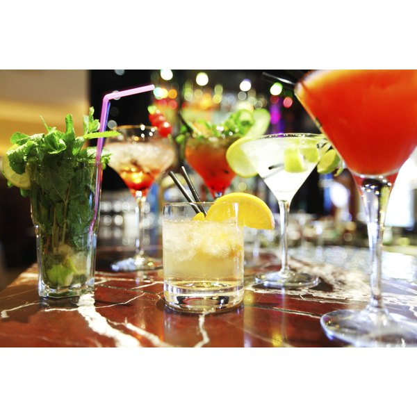 An assortment of colorful cocktails on a bar.