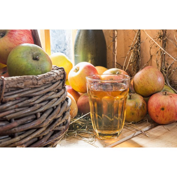 A glass of water mixed with Bragg vinegar sits on a wooden counter in front of a basket of apples.