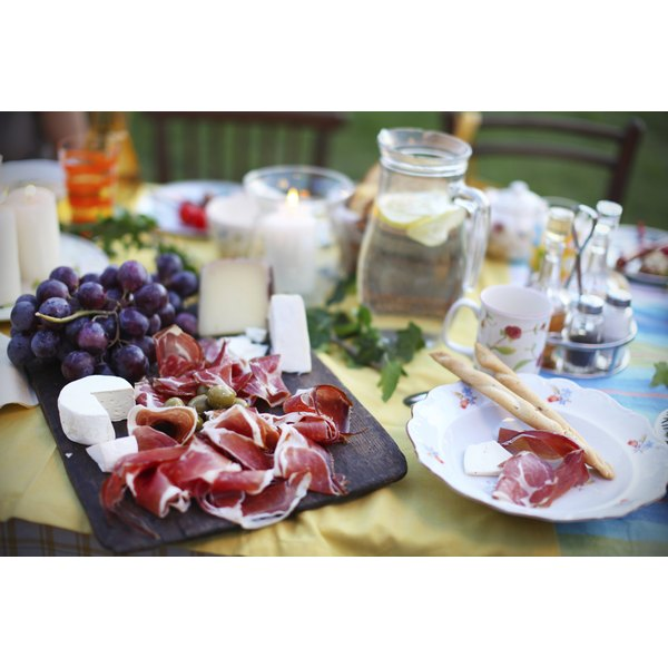Prosciutto, grapes and cheese on a tuscan picnic spread.