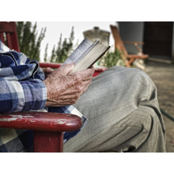 Close-up of an elderly man's hands as he reads the Bible.