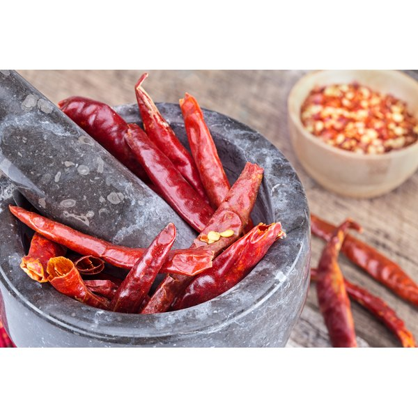 Dried cayenne peppers in a mortar and pestle.