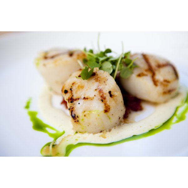 Group three grilled bay scallops on a small plate for a delicious appetizer.