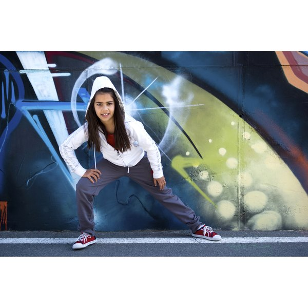 A girl stands before a spray paint art wall and is poised to dance.