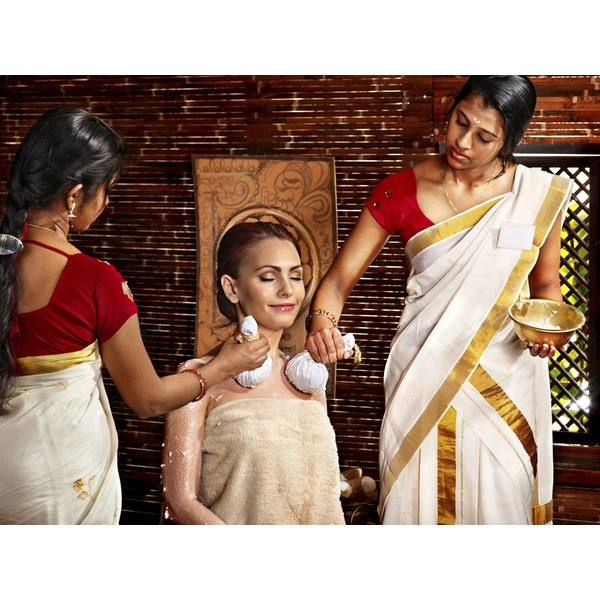 A woman receives an Ayurvedic massage from two women.