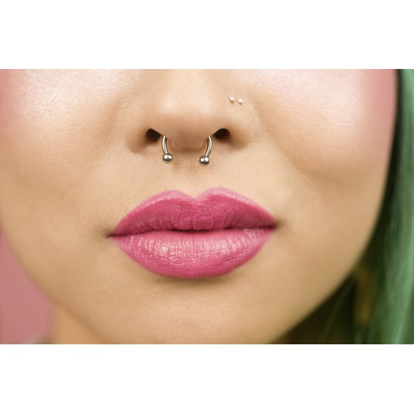 A young woman with multiple nose piercings.