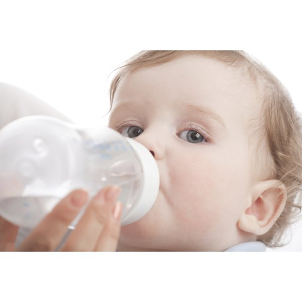 A toddler is drinking from a water bottle.
