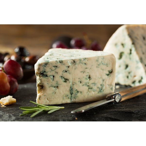 A large block of blue cheese on a cutting board.