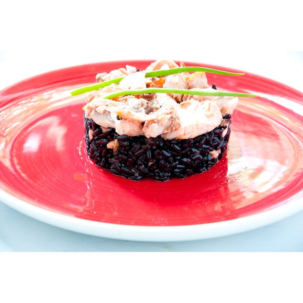 A bed of cooked black rice holds a salmon cream dish atop it.