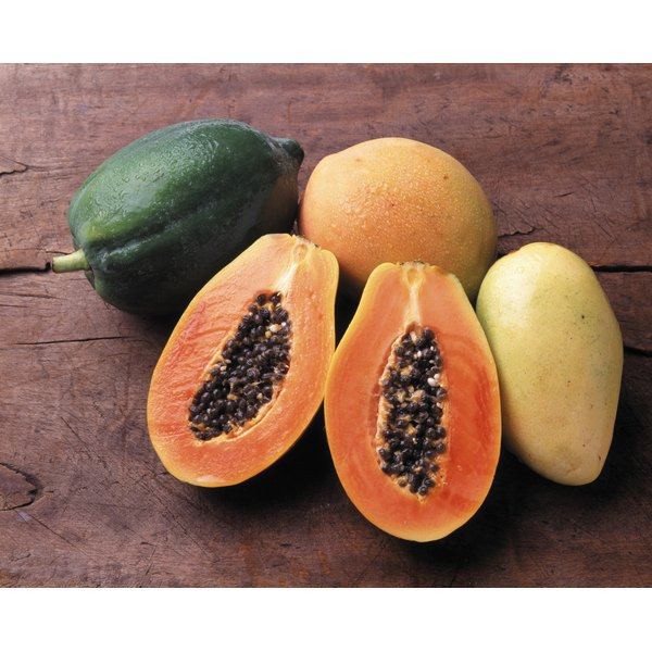 Whole and halved papayas on a wood table.