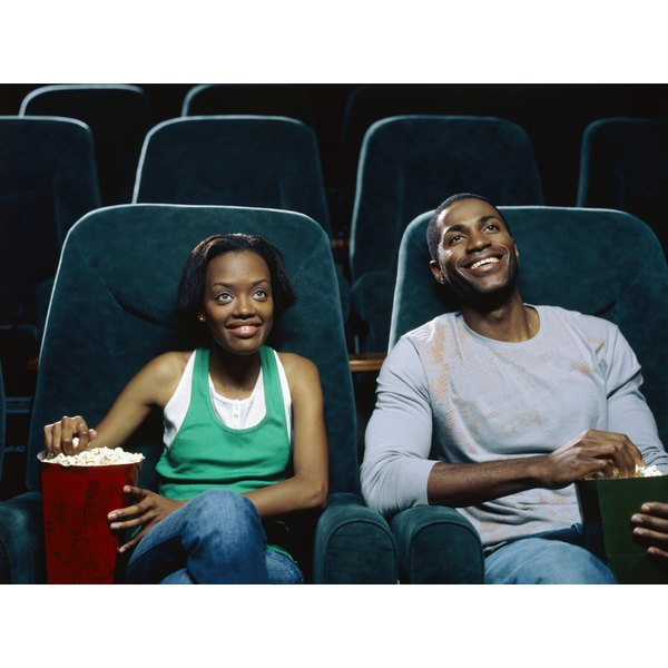 Young couple watching movie in theater, eating popcorn.