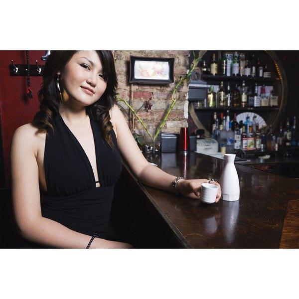 A woman is drinking sake.