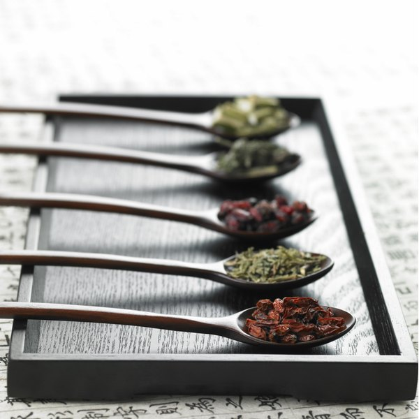 Different dried herbs in spoon.