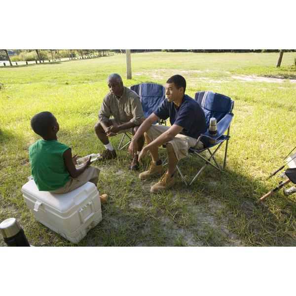 Two men and a boy conversing at a picnic in the park.