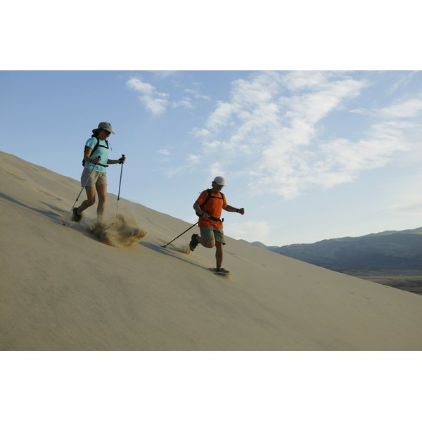 A man and woman are hiking through the sand dunes.