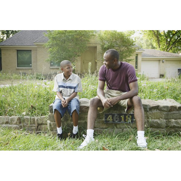 Surrogate father speaking to young boy in backyard.
