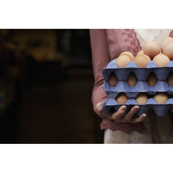 Close-up of a woman holding multiple crates of eggs.