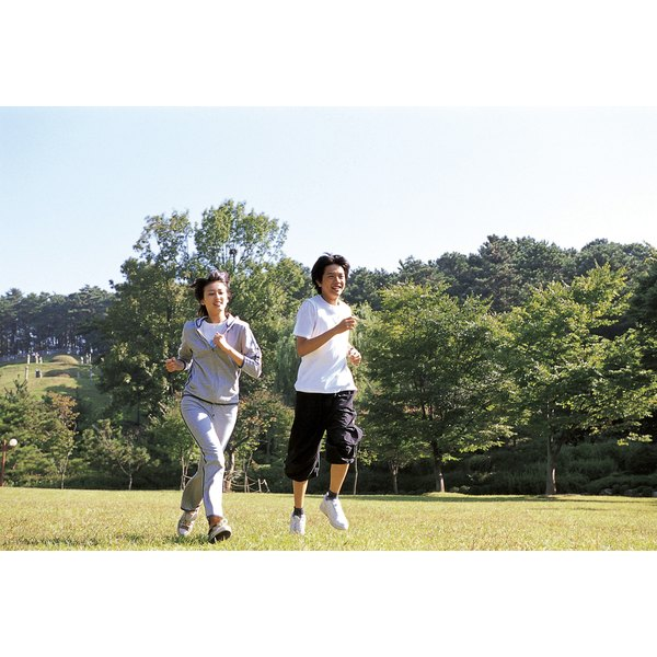 A couple takes a jog together through a grassy lawn in the park.