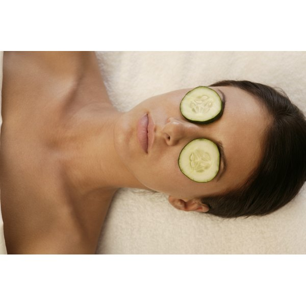 A woman relaxing with fresh cucumber slices on her eyes.