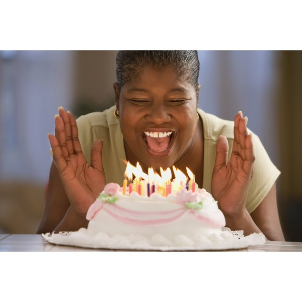 Woman blowing out birthday candles on cake.