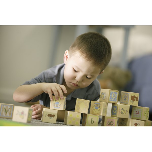 Child playing with blocks in nursery.