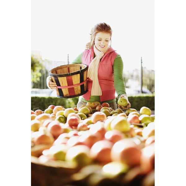 Woman selecting apples at farmer's market.