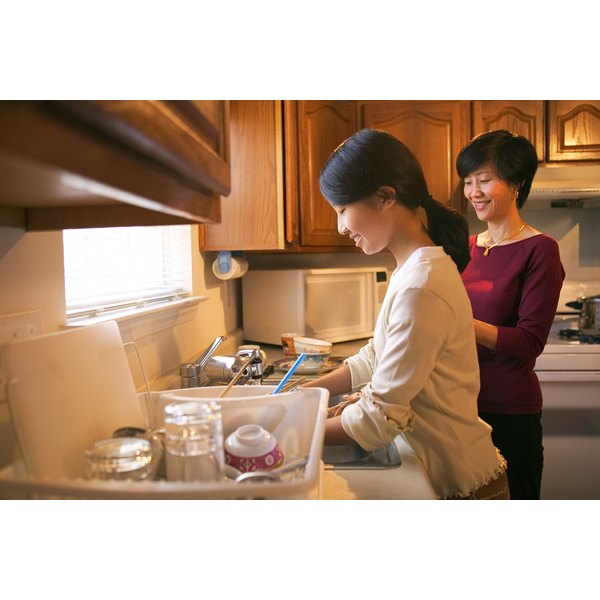A teenager helps her mother in the kitchen by doing the dishes in the sink.