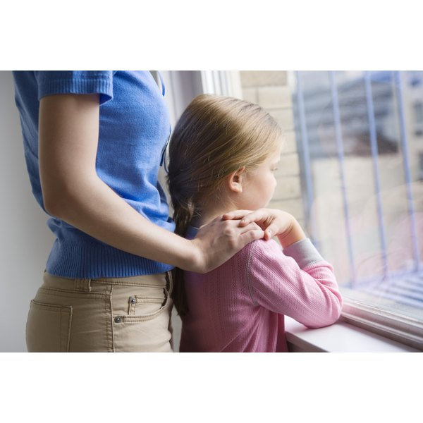 Woman touching her daughter on the shoulder and staring out the window.