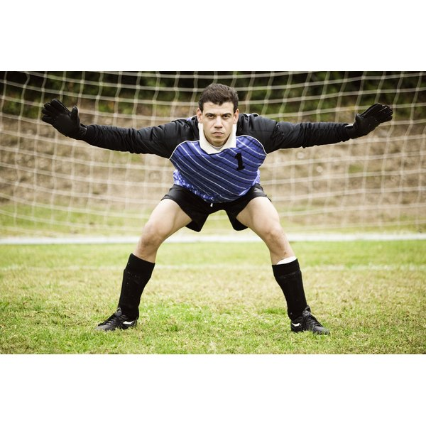 A male goalkeeper guarding the soccer goal.