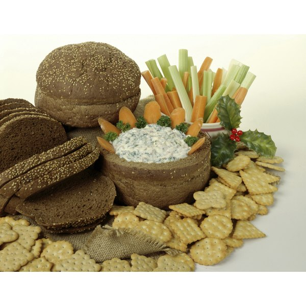 A healthy snack arrangement with whole grain crackers and bread around a creamy dip and fresh-cut vegetables.