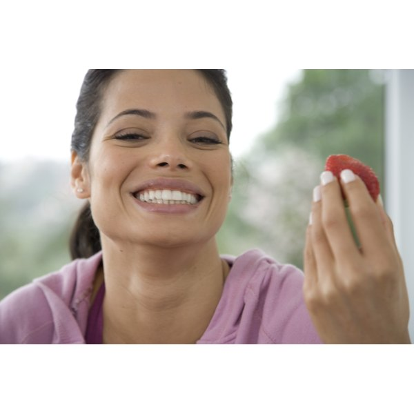 Young woman smiling while holding a strawberry.