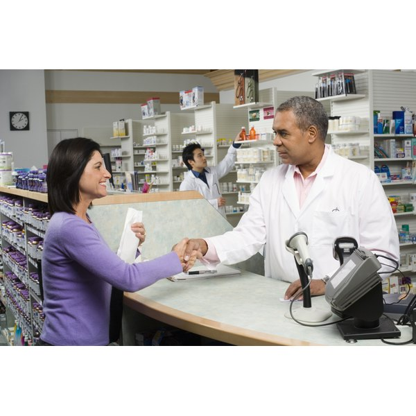 Pharmacist shaking hands with a woman in pharmacy.