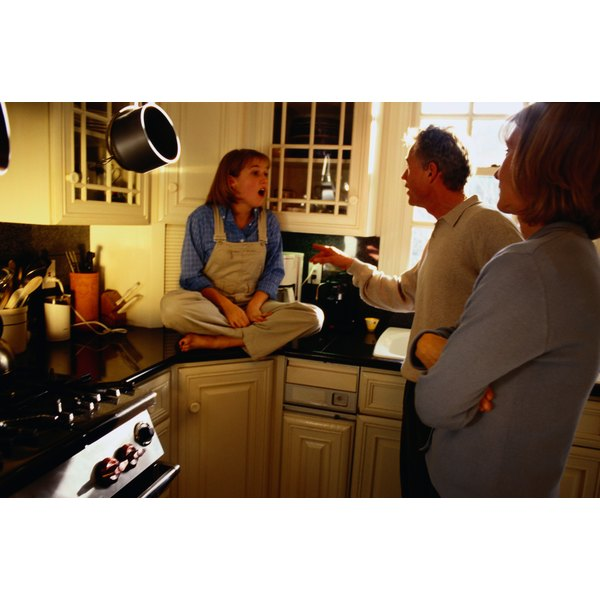 Parents argue with their daughter in the kitchen with the father pointing his finger at the daughter, mother stands back with arms folded.