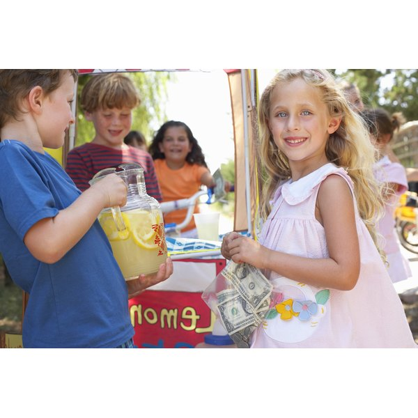 Young children are running a lemonade stand.