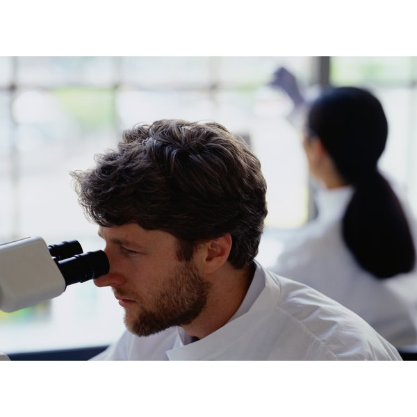 A man is looking through a microscope.