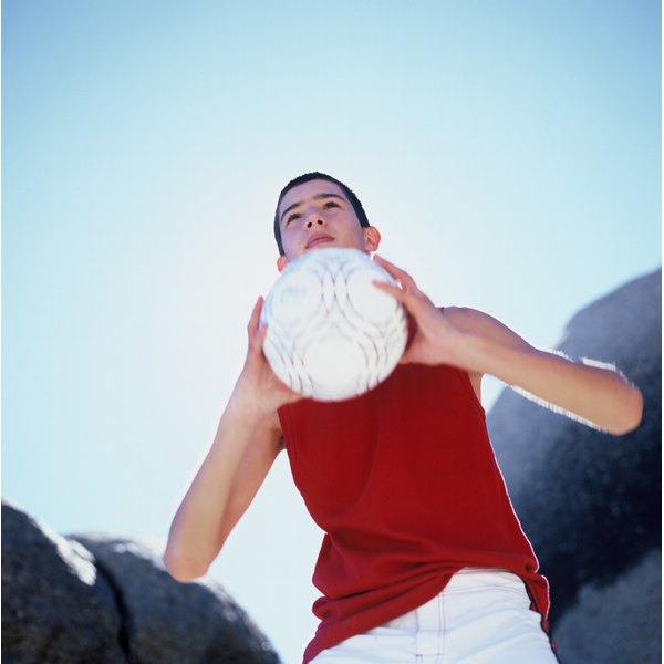 Teenage boy holding a volleyball.