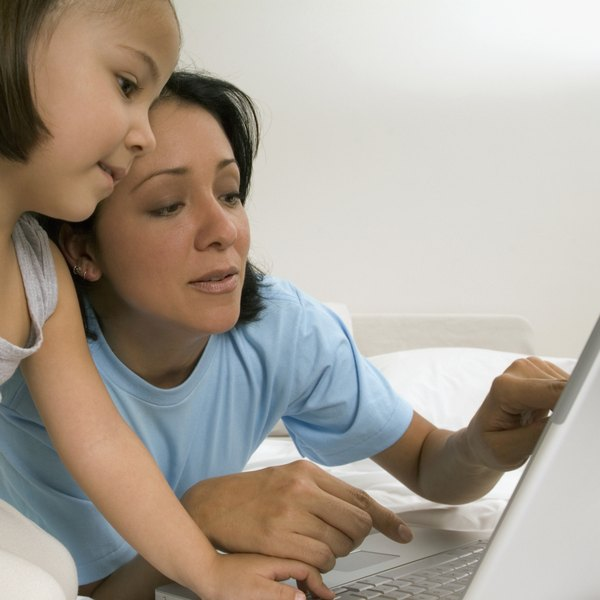 Woman and girl using laptop on bed, close-up